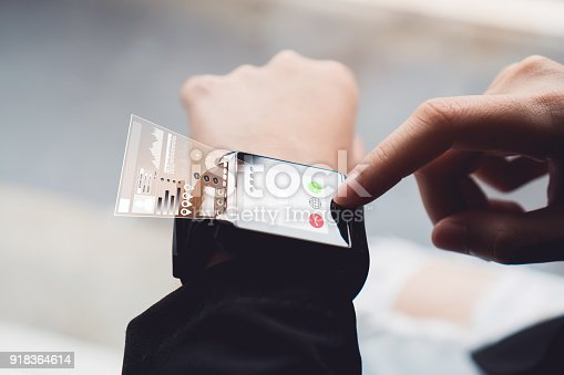 istock Woman using touch digital clock in the display and technology advances in communication. This is a new technology. That makes life more comfortable. 918364614