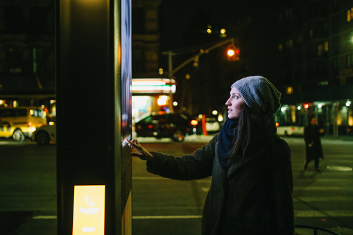 Young woman using interactive touch screen city display to check for information, New York City, USA.