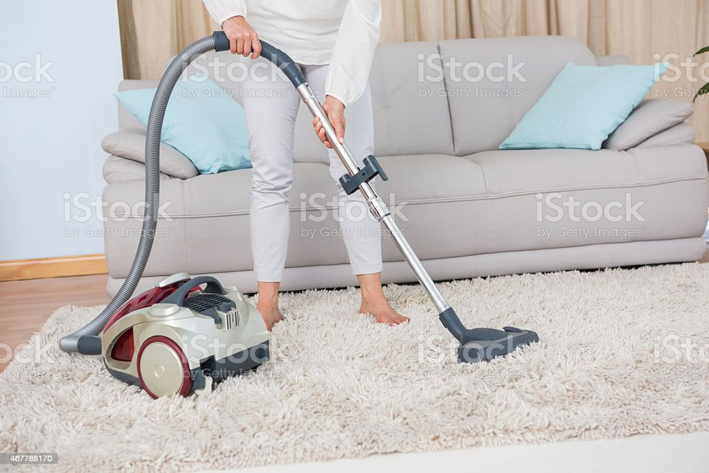 Woman using vacuum cleaner on rug stock photo