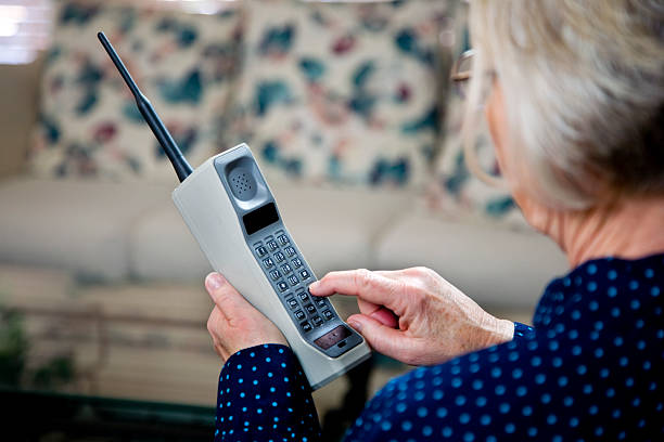 Woman using vintage brick cell phone stock photo
