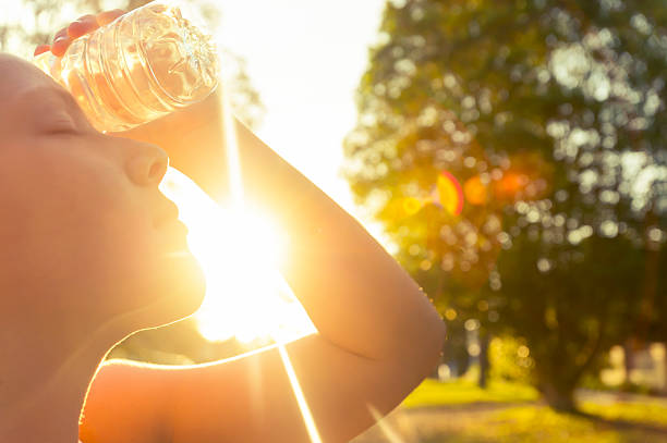 woman using water bottle to cool down. - warmte stockfoto's en -beelden