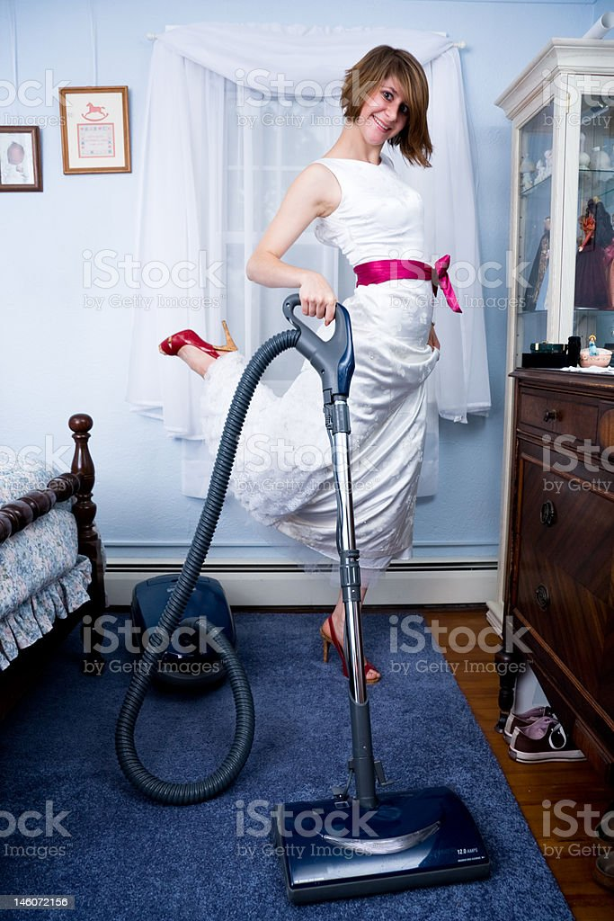 Woman vacuuming bedroom wearing formal gown royalty-free stock photo