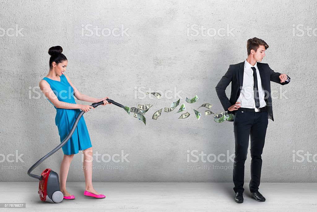 Woman vacuuming money out of man's pocket stock photo