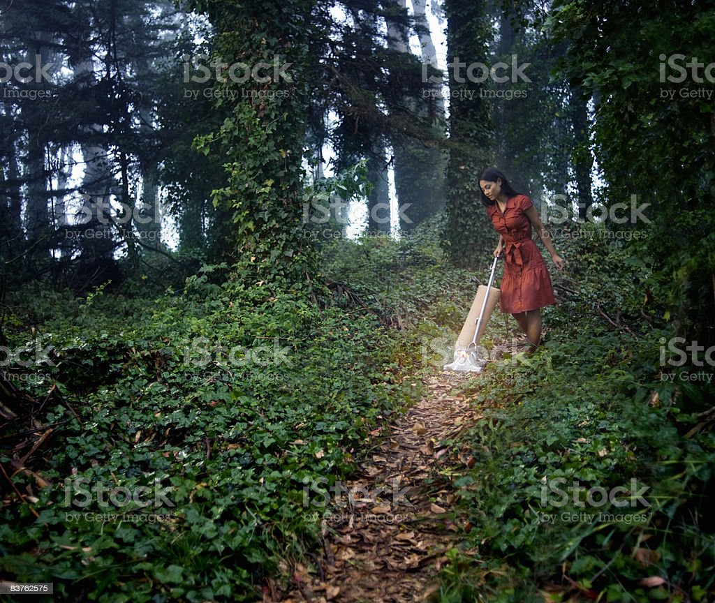 Woman vacuuming path in ivy covered forest royalty-free stock photo