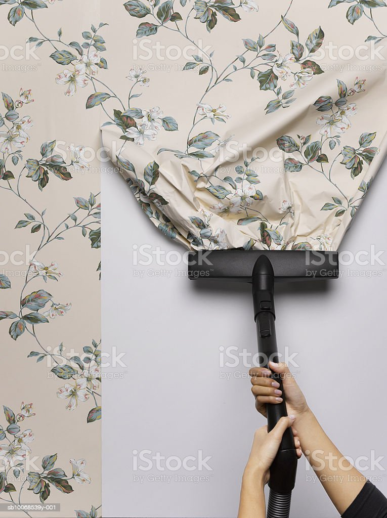 Woman vacuuming wallpaper from wall, close-up royalty free stockfoto