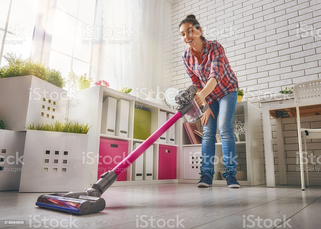 Woman vacuums the floor stock photo