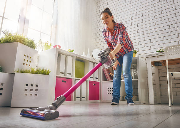woman vacuums the floor - stofzuiger stockfoto's en -beelden