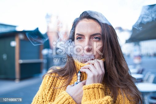 Caucasian woman vaping electronic cigarette outdoors.