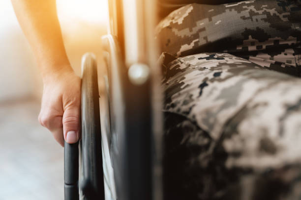 woman veteran in wheelchair returned from army. close-up photo veteran woman in a wheelchair. - sedia a rotelle foto e immagini stock