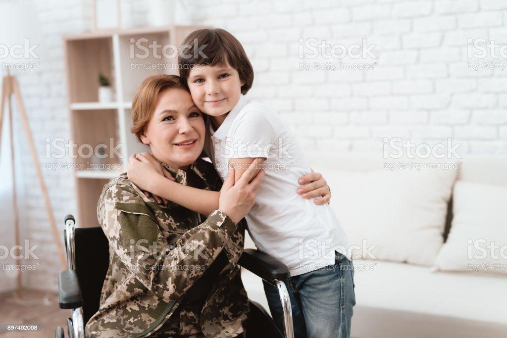 Veterano de la mujer en silla de ruedas volvió a casa. Hijo abraza a mamá en silla de ruedas. - foto de stock