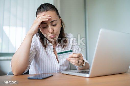 857213750istockphoto Woman victim of credit card fraud 1169720901