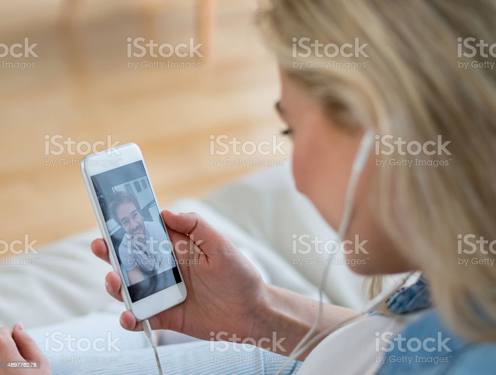Woman video chatting on her cell phone stock photo