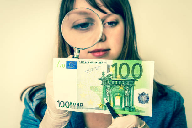 woman viewing counterfeit banknote with magnifying glass - watermark stock photos and pictures