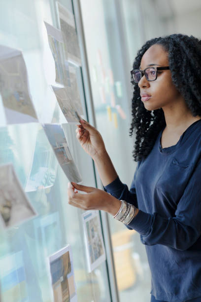 Frau sieht Layouts auf Büroglasfenster – Foto