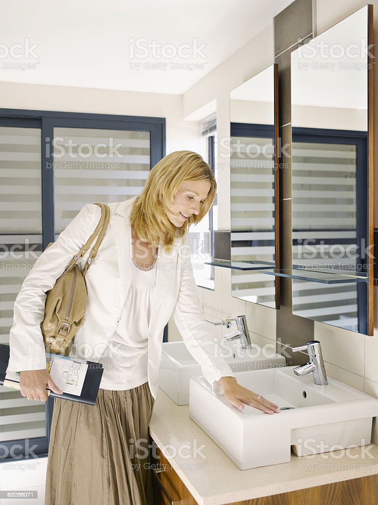 Woman viewing sink in design showroom royalty free stockfoto
