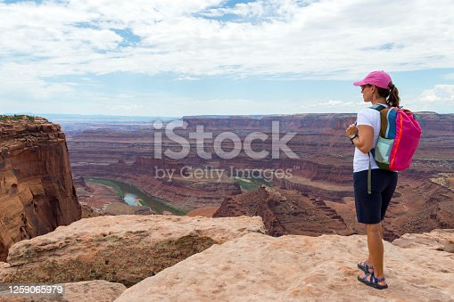 This shot shows a beautiful young woman viewing the end of the mesa in Dead Horse Point State Park in Utah.  The green Colorado River below flows through red rocky canyons that twist and loop.  The overcast sky casts shadows on the water and canyon walls.