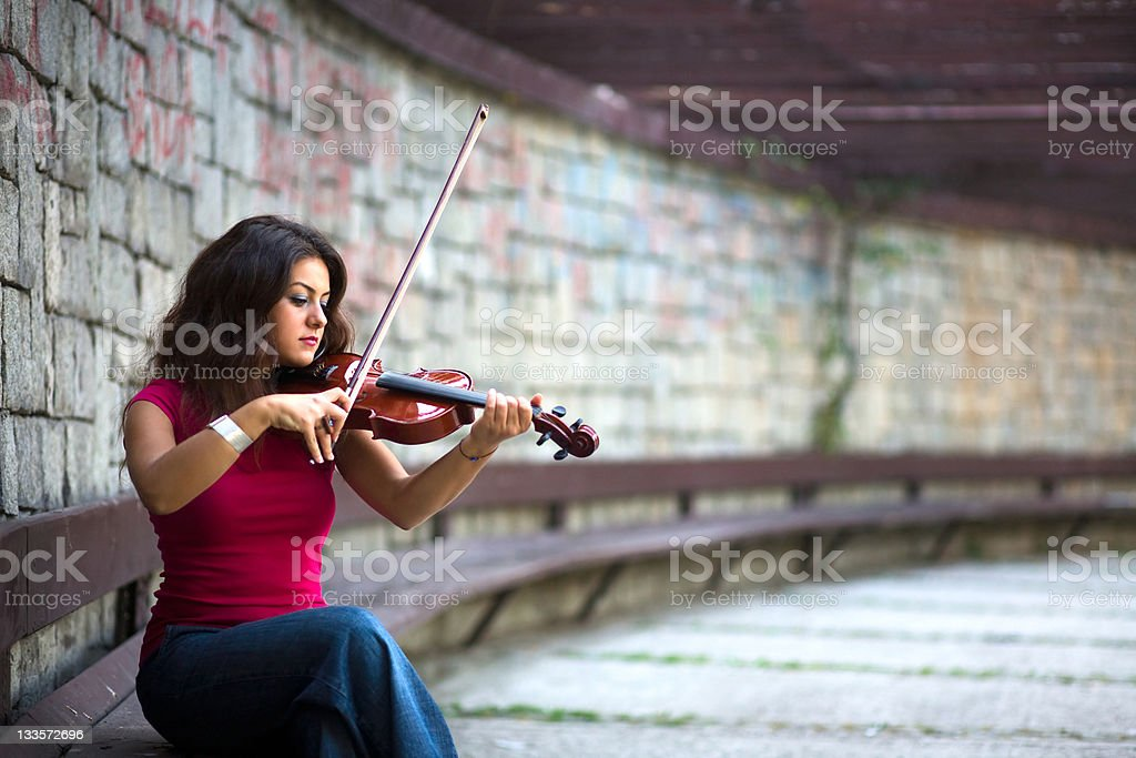 Woman violinist playing in enclosed brick area stock photo