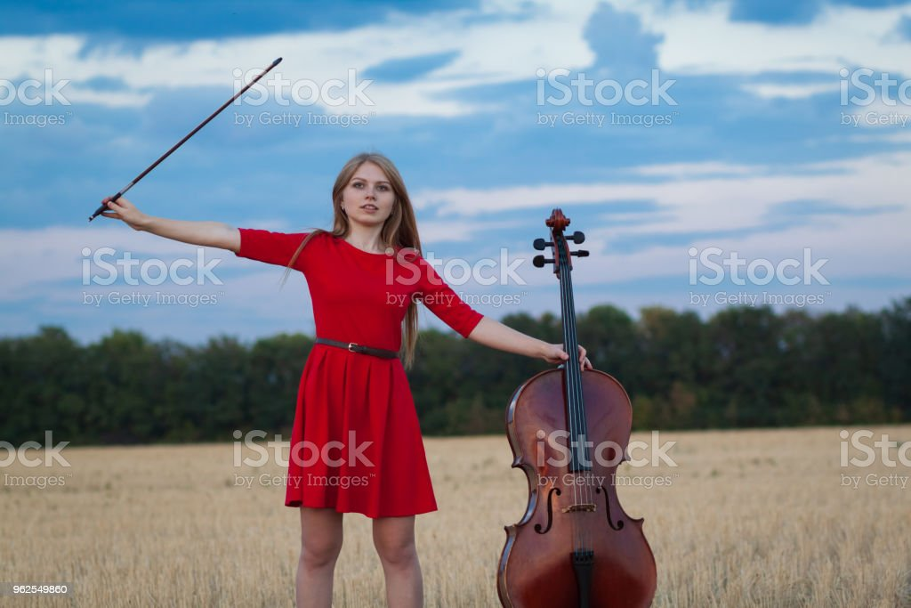 Woman violoncellist with cello and bow playing in field - Royalty-free 20-24 Years Stock Photo