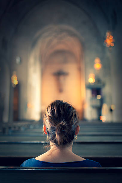 Woman visiting a christian church A woman sitting in a bench row in a large old christian church. catholicism stock pictures, royalty-free photos & images