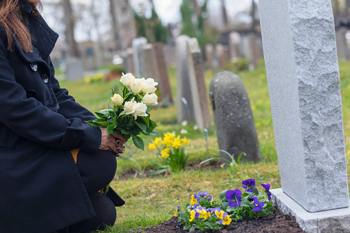 A woman with flowers kneeling by a grave at the cemetery.