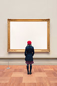 Woman visiting an unidentifiable gallery with a large painting. Clipping path included for the frame.