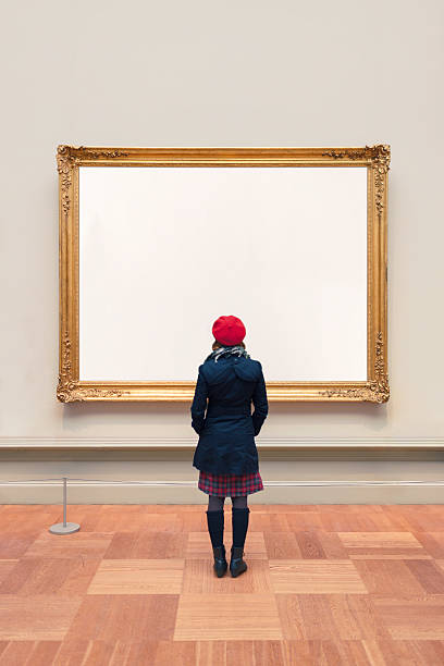 Woman visiting an Unidentifiable Gallery Woman visiting an unidentifiable gallery with a large painting. Clipping path included for the frame. critic stock pictures, royalty-free photos & images