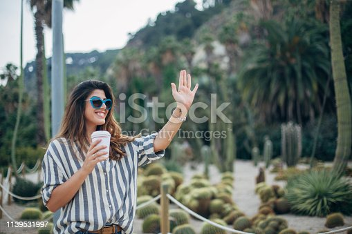 Beautiful woman standing and holding cup of coffee in botanical garden