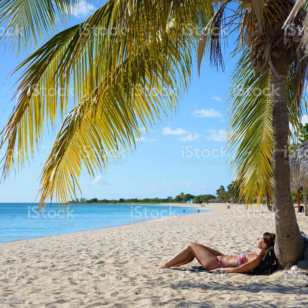 Woman visiting Cuba sunbathing on beach at Playa Ancon stock photo
