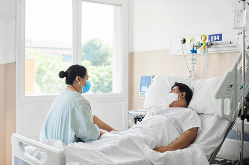 Woman visiting male patient in hospital ward. Female is sitting by man lying on bed. They are at hospital during COVID-19 epidemic.