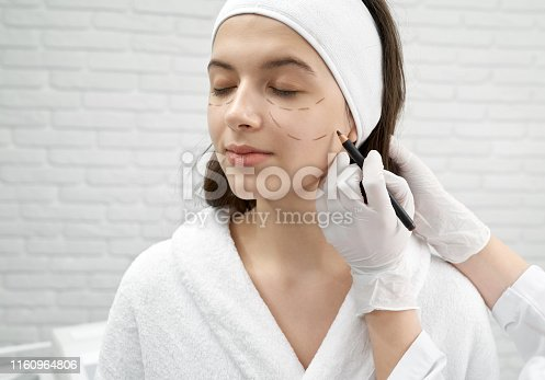istock Woman visiting surgeon and doing lifting on face in clinic 1160964806