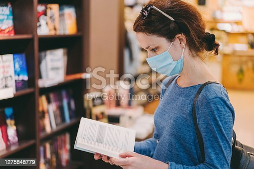 Woman with protective face mask reading a book in the bookstore
