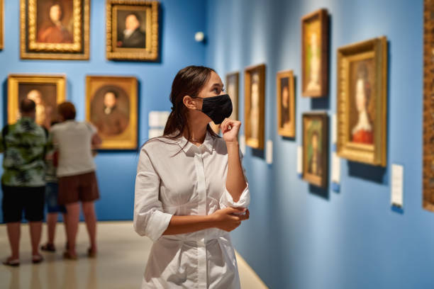 woman visitor wearing an antivirus mask in the historical museum looking at pictures. - museu imagens e fotografias de stock