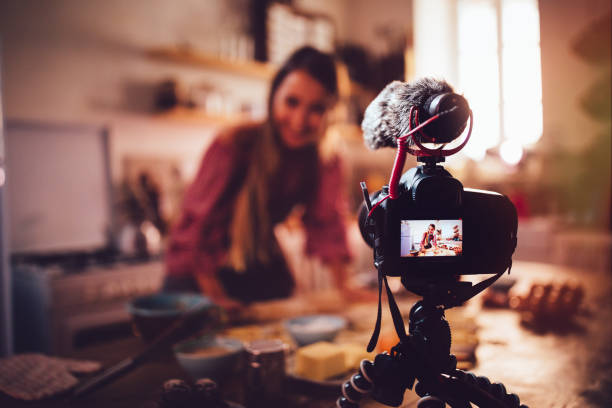Woman vlogger baking and recording video for food channel Woman food vlogger preparing pastry recipe and filming on camera for food channel sea channel stock pictures, royalty-free photos & images