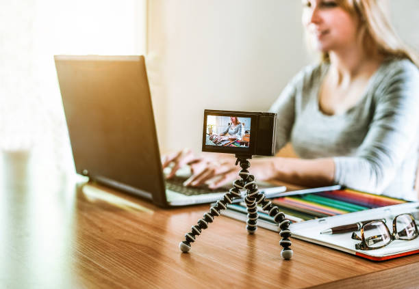 Woman vlogger looking using laptop computer and filming on video her life - New job trends concept - Girl sharing on internet social networks lifestyle contents - Focus on tripod camera - Warm filter stock photo