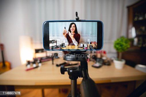 Youg caucasian cute woman vlogging about makeup.