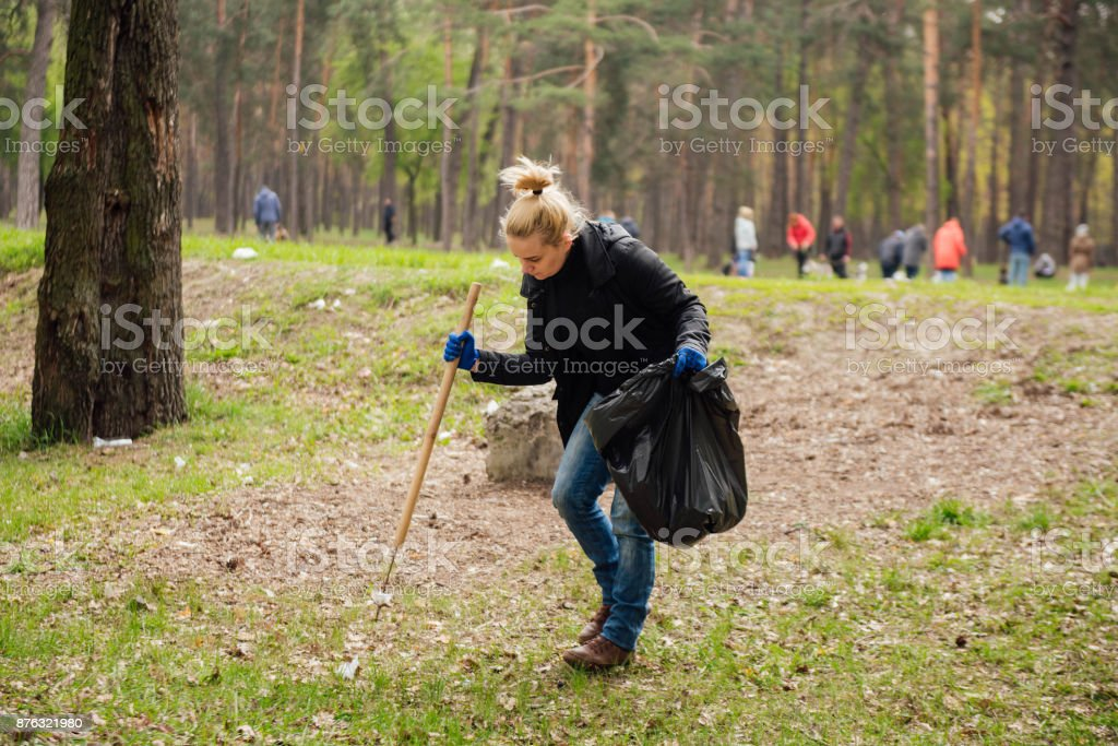 Woman volunteer collecting garbage in park stock photo