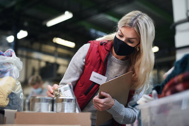 Woman volunteer in community charity donation center, food bank and coronavirus concept. stock photo