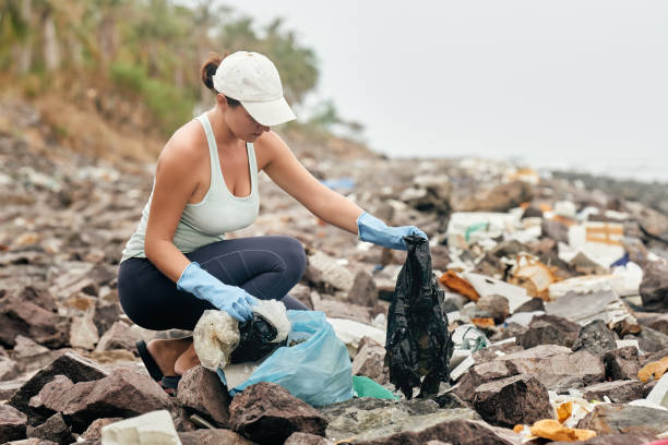 Woman volunteer in gloves holds plastic garbage on the background of sea coast. stock photo