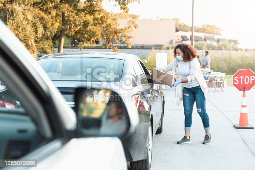 During the COVID-19 pandemic, a mid adult woman gives a box of donated food to someone in a car. She is volunteering at a drive-through food drive. She is wearing protective gloves and a protective face mask.