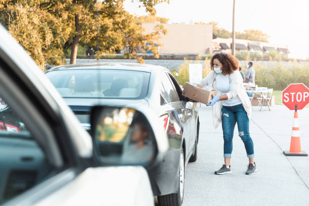 Woman volunteers at drive-through food drive stock photo