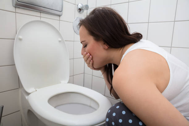 Woman Vomiting In Toilet Bowl stock photo