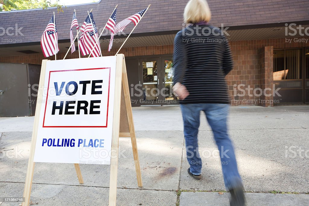 Woman Voter Entering Voting Polling Place for USA Government Election stock photo