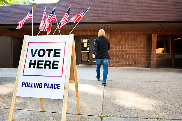 woman voter entering voting polling place for usa government election - vote sign stock photos and pictures