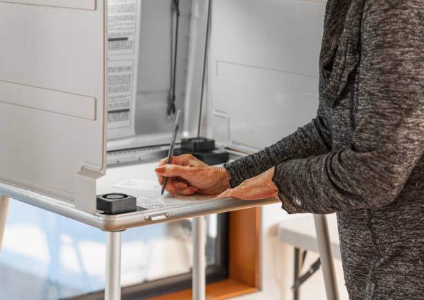 woman voting polling election: woman voting in room at polling place for elections of measures, primary, midterm and presidential elections - kryć zdjęcia i obrazy z banku zdjęć