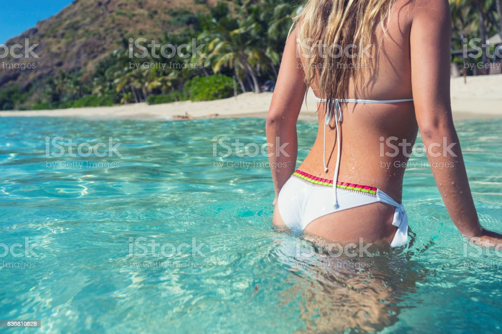 Woman wading in turquoise water on a tropical beach. stock photo