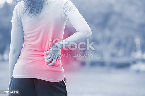 istock woman waist injury in park 628524394