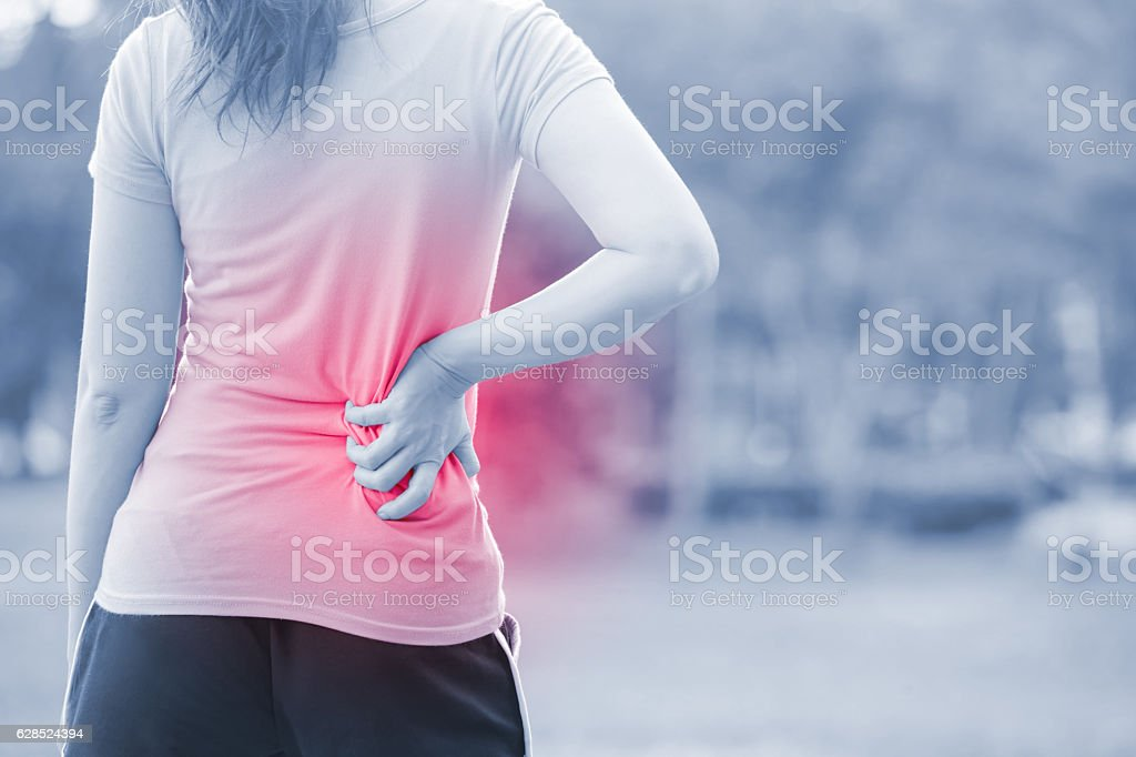 woman waist injury in park stock photo