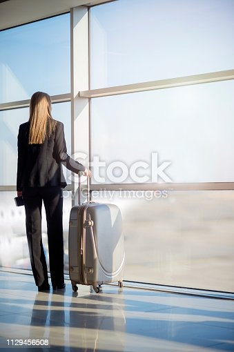 512522378 istock photo Woman waiting at the airport 1129456508