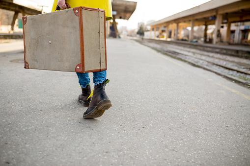young girl walking along railway station,