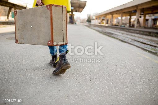 young girl walking along railway station,